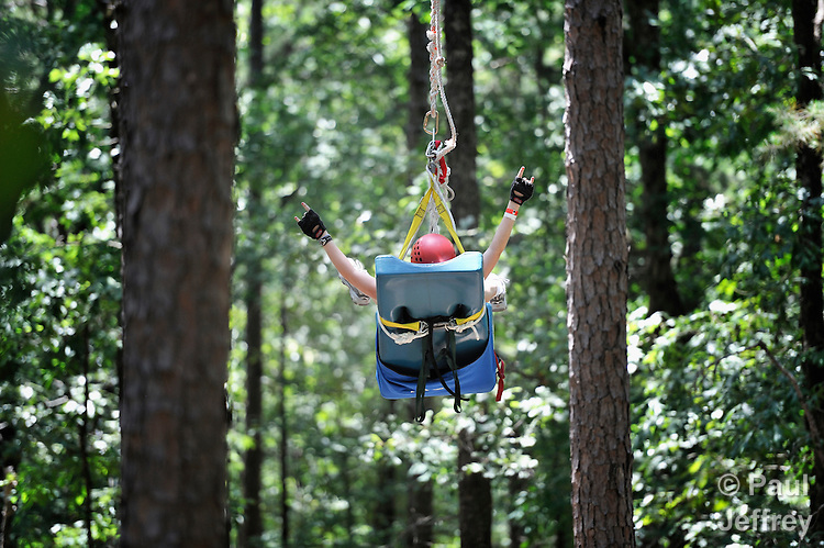Maggie Wilson, a camper at Camp Aldersgate in Little Rock, Arkansas, rides a zip line through the forest canopy. The camp, supported by United Methodist Women, offers children suffering from a variety of disabilities a safe and fun experience similar to that which normally-abled children often enjoy.