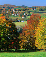 Caledonia County, VT<br /> Peacham village in a valley of green meadows with forested hills in autumn colors