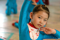 A young Uyghur girl practices a traditional dance at a school in Urumqi. Dolan is an ancient Uyghur folk dance popular in China's Xinjiang Uygur Autonomous Region. Dancers are accompanied by tambourines and plucked stringed instruments called Kalun and rawap. Dolan is an ancient name for Uyghurs living in several places in the Tarim Basin..