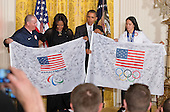 Jon Lujan of Littleton, Colorado, Paralympics Alpine Skiing, a former United States Marine Corps Sergeant and 2014 Winter Paralympic Games Opening Ceremony Team USA Flag Bearer, left, and Julie Chu of Fairfield, Connecticut, Women's Ice Hockey and 2014 Winter Olympic Games Closing Ceremony Team USA Flag Bearer, right present signed flags to United States President Barack Obama and First Lady Michelle Obama during the welcome ceremony honoring the United States teams and delegations from the 2014 Olympic and Paralympic Winter Games in Sochi to the White House in Washington, D.C. on Thursday, April 3, 2014.<br /> Credit: Ron Sachs / Pool via CNP