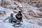 Two Bedouins making tea on the cliffs of Petra, Jordan. Petra is the most visited tourist attraction in Jordan, a symbol of the country for its historical and archaeological importance. It has been a UNESCO World Heritage Site since 1985. The Bedouin families that have been living for centuries in the caves of Petra, agreed to move out into a small village, built near the site of Petra. Most of them earn their living from tourism which seems to be the only option available, especially for the younger generations.