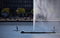 23rd April 2020, Hamburg, Germany: Stand-up paddlers on their way in bright sunshine on the Binnenalster behind the Alster fountain in front of the Jungfernstieg during the corona virus pandemic