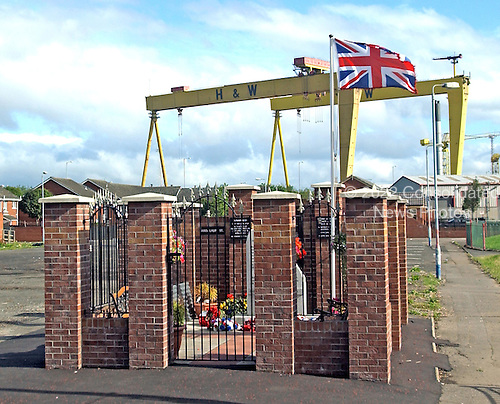"Belfast, Northern Ireland - August 14, 2005 -- Cranes that are used to lift large ships put of the water at the Harland and Wolff shipyard in the harbor of Belfast, Northern Ireland loom over a loyalist memorial on Sunday, August 14, 2005.  Many famous ships, including the ""Titanic"" were built in this shipyard..Credit: Ron Sachs / CNP"