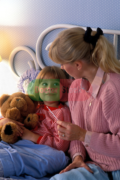 mother sitting at bedside holding oral thermometer talking to her sick young girl in bed holding her teddy bear