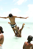 MAURITIUS, a boy dives off of his fathers shoulders and into the Indian Ocean, the beach at Ile aux Cerfs Island