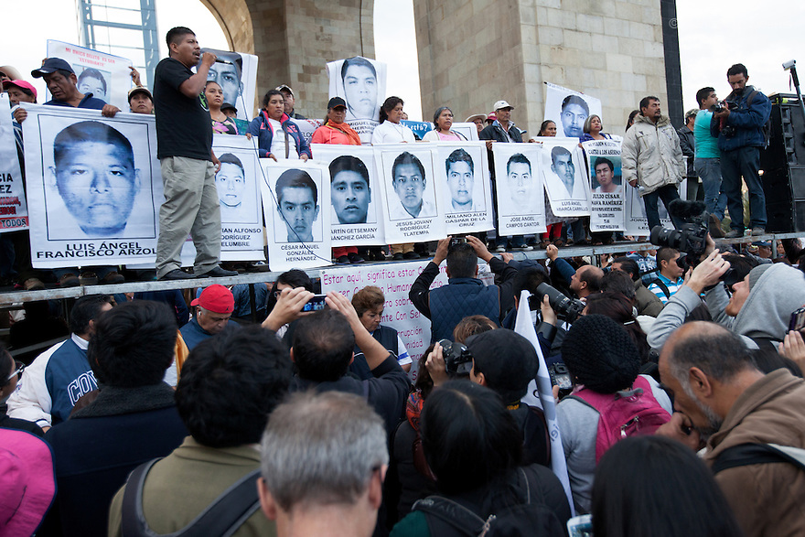 Parents and relatives of the missing students from Ayotzinapa's teacher training college, stood on a platform in front of the The Monument to the Revolution holding images of the missing students during a march to markthe three monthssince the disappearance of 43 Ayotzinapa's teaching college students in Mexico City on December 26, 2014. The 43students went missingon Sept. 26 after confrontations in which police gunfirekilled six peopleandwoundedat least25inIguala, in Guerrero state. Alexander Mora Venancio, one of the 43 missingstudentsof Ayotzinapa, has been identified and confirmed dead by authorities. Many are demanding justice and that the search for the 42 missing students continue until there is concrete evidence to the contrary. Mexico – officially - lists more than 20 thousand people as having gone missing since the start of the country's drug war in 2006, and the search for the missing students has turned up other, unrelated mass graves.(Photo by BenedicteDesrus)