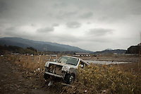 A vehicle lies in a ditch on the side of a road. Thousands of people died in this small town which ran out of body bags. On 11 March 2011 a magnitude 9 earthquake struck 130 km off the coast of Northern Japan causing a massive Tsunami that swept across the coast of Northern Honshu. The earthquake and tsunami caused extensive damage and loss of life.