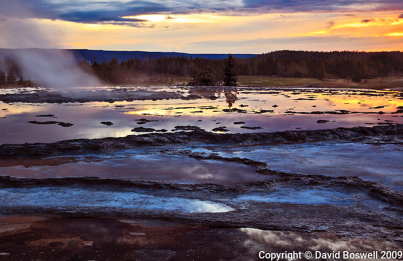 The setting sun reflects in the calm waters of a silent Great Fountain Geyser in the Lower Geyser Basin of Yellowstone National Park.