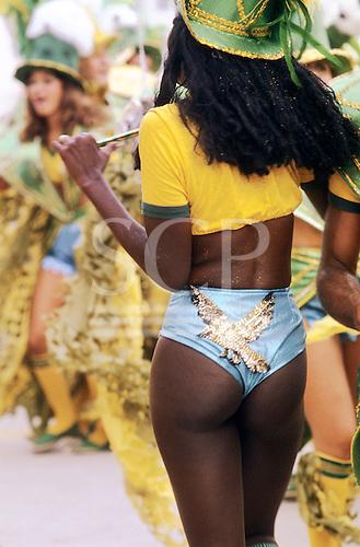 Rio de Janeiro, Brazil. Carnival - girl wearing skimpy metallic blue shorts with gold bird motif and Brazil colours top.