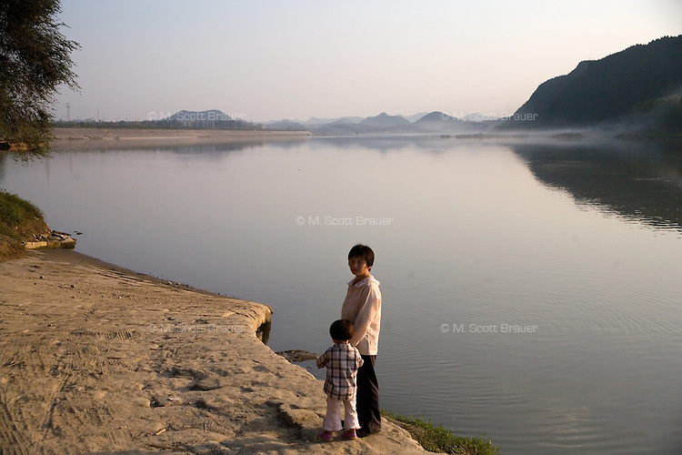A woman and child wait for a ferry in Langzhong, Sichuan, China.