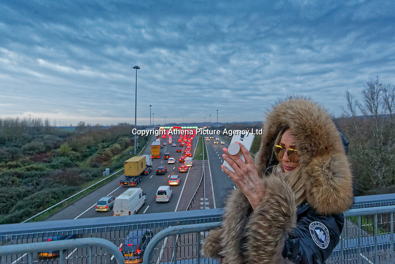 Pictured: A woman stands on a bridge to take a selfie on her mobile phone while long queues of cars form by the Severn Bridge tolls on the westbound carriageway of the M4 in south Wales, UK. Friday 14 December 2018<br /> Re: Work to remove the toll booths on the Severn bridges has commenced as the two motorway crossings into south Wales are becoming toll free.<br /> Motorists have been warned their journeys into south Wales may be affected as the M4 Prince of Wales bridge will shut westbound for the next three nights.<br /> The tolls have been in place since the first crossing opened in 1966, but will be removed on Monday.
