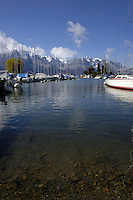 Boats moored on Lake Léman, with snow covered mountains in the background. Clarens close to Montreux, Switzerland.