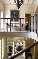 A view from the staircase into the dining room on the ground floor and a landing furnished with a cane-backed sofa on the first floor