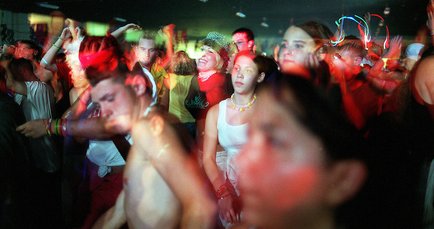 The crowd throbs in rhythm to the pulsing beat djs mix at the second annual Revolution in a roller rink in Dayton during the early hours of July 4, 2001. The event drew a crowd of several thousand from across the region and is one of the largest raves in Ohio. (Danny Gawlowski/ The Plain Dealer)