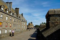 Tourists walk along the promenade of the ramparts of the old city, Saint Malo, Brittany, France.