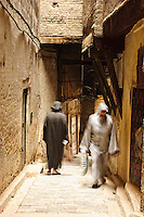 Thousands of people still enjoy the very picturesque yellow and narrow streets of the medina of Fez, Morocco.