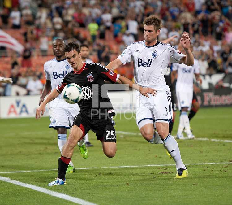 Alain Rochat (25) of D.C. United keeps control of the ball in front of Brad Rusin (3) of the Vancouver Whitecaps during a Major League Soccer match at RFK Stadium in Washington, DC. D.C. United lost to the Vancouver Whitecaps, 1-0.