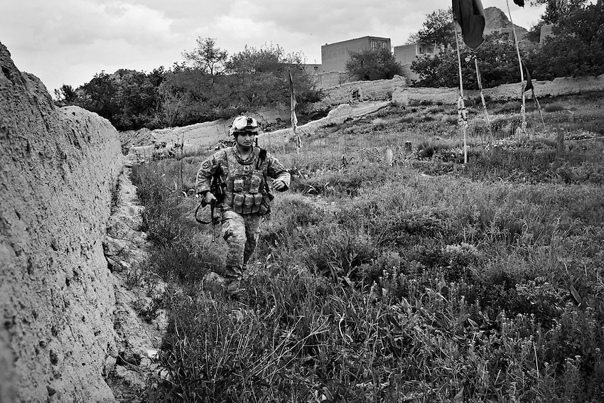A member of Bravo Company, 1-32 Infantry, 3rd Brigade, 10th Mountain Division, runs through an orchard during an ambush by the Taliban in Charkh, Afghanistan, Sunday, May 3, 2009. One member of the platoon was injured during the attack.
