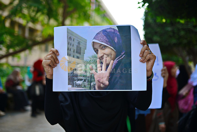 An Egyptian student who support Muslim Brotherhood and ousted President Mohammed Morsi, hold a picture of her fellow Radwa Jamal, during a demonstration against her arrest by Egyptian police, at Cairo University on November 5, 2014. Photo by Amr Sayed