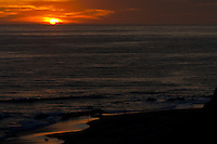 Sun setting behind oil rigs, seen from Crystal Cove State Park.