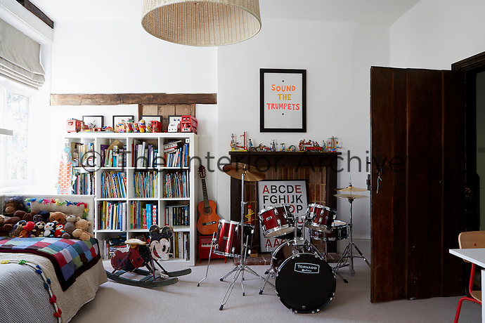 A child's bedroom with a red drum kit and single bed with cuddly toys. White shelves are packed with brightly coloured books. The wooden fireplace features a large framed alphabet picture.