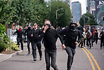 Protestors run away from Seattle Police after trying to find an alternative route to the Patriot Prayer event during the Solidarity Against Hate rally Sunday August 13, 2017 in Seattle.
