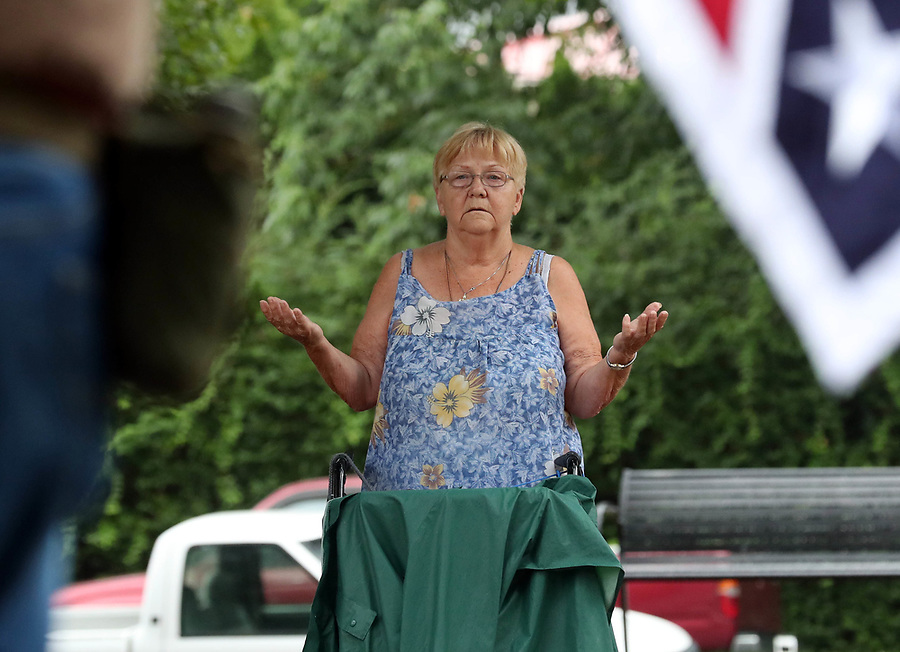 Charlottesville resident Flo Tinsley prayers near Allen Armentrout of North Carolina who stood wearing a Confederate outfit with 2 protecting the Lee Statue Tuesday, Aug. 15, 2017 at Emancipation Park in Charlottesville, Va. A small crowd of Charlottesville residents protested him for 30 minutes before Police escorted Armentrout away from the park. Photo/Andrew Shurtleff