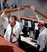 "In Firing Room 4 of the Launch Control Center, employees wave American flags after the successful launch of Space Shuttle Discovery on mission STS-121.  Liftoff was on-time at 2:38 p.m. EDT.  During the 12-day mission, the STS-121 crew of seven will test new equipment and procedures to improve shuttle safety, as well as deliver supplies and make repairs to the International Space Station. Landing is scheduled for July 17 at Kennedy's Shuttle Landing Facility. Photo Credit: ""NASA/Bill Ingalls"""