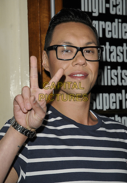 "GOK WAN.The ""Thriller Live"" 1000th performance, Lyric Theatre, Shaftesbury Ave., London, England..May 26th, 2011.headshot portrait white hand v peace sign black beige blue grey gray striped stripes glasses .CAP/CAN.©Can Nguyen/Capital Pictures."