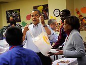United States President Barack Obama packs and delivers bags of food to area residents, with the help of his Mother-in-law Marian Robinson at Martha's Table on Wednesday, November 24, 2010, in Washington, DC.  .Credit: Leslie E. Kossoff - Pool via CNP