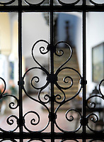 The metalwork of a wrought-iron grille forms multiple heart shapes