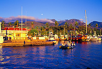 Tourists return to Lahaina Harbor on a tender at sunset with a full moon above the West Maui Mountains. In the foreground is the main loading dock and the Pioneer Inn.