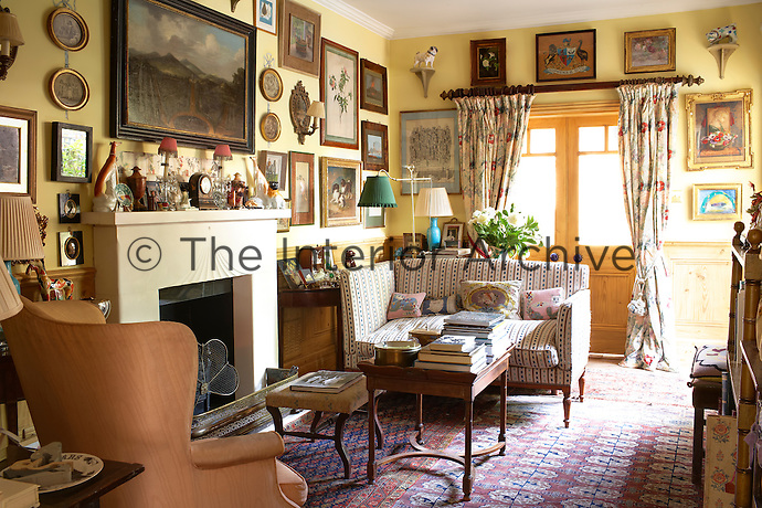 A cosy, informal sitting room decorated in a vibrant yellow. A small sofa and a wingback armchair stand either side of the simple fireplace. The room has floral pattern curtains hanging at a pair of double doors. A collection of artworks and ornaments are displayed around the room.