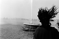 "Switzerland. Geneva. The famous ""Jet d'eau "" on the lake Geneva ( also called Lac Léman). Woman's dark long curly hair blowing in the wind.The Jet d'Eau (Water-Jet) is a large fountain in Geneva and is one of the city's most famous landmarks. Situated at the point where Lake Geneva empties into the Rhône, it is visible throughout the city. Five hundred litres of water per second are jetted to an altitude of 140 meters  by two 500 kW pumps, operating at 2,400 V, consuming one megawatt of electricity. The water leaves the 10 centimeters nozzle at a speed of 200 kilometrers per hour. At any given moment, there are about 7,000 litres  of water in the air. © 1987 Didier Ruef"