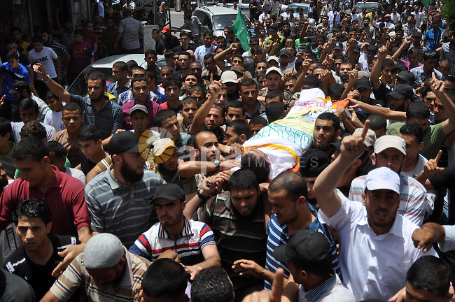 Palestinian mourners carry the body of Hussein Massoud, 30, a member of civil defense who was killed during the rescue operation of five militants of Hamas movement, in Rafah in the southern Gaza Strip, June 20, 2014. Five members of the Qassam Brigades, the armed wing of Palestinian resistance faction Hamas, were killed on Thursday inside an underground tunnel in the eastern Gaza Strip, a source close to Hamas said. Photo by Eyad Al Baba