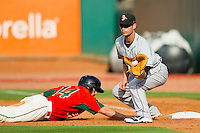 Connor Narron (43) of the Delmarva Shorebirds fields a pick-off throw as Tony Caldwell (14) of the Greensboro Grasshoppers dives back into first base at NewBridge Bank Park on May 26, 2013 in Greensboro, North Carolina.  The Grasshoppers defeated the Shorebirds 11-2.  (Brian Westerholt/Four Seam Images)