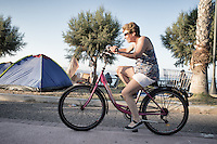 Tourist pedaling her bicycle past a makeshift refugee encampment. Kos, Greece. Sept. 5, 2015