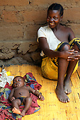 Kasanga, Tanzania. Mother with a baby on a mat next to her; Lake Tanganyika.