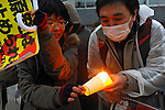 "Tokyo, Japan - March 11: A man tried to give his fire to a woman's candle in front of the Diet Building at Chiyoda, Tokyo, Japan as a demonstration against nuclear power on March 11, 2012. More than 10,000 people held the candles and hands of next people to make a ""Human Chain."" As this day was one year anniversary of Great East Japan Earthquake and Tsunami, there were many demonstrations held in the city."