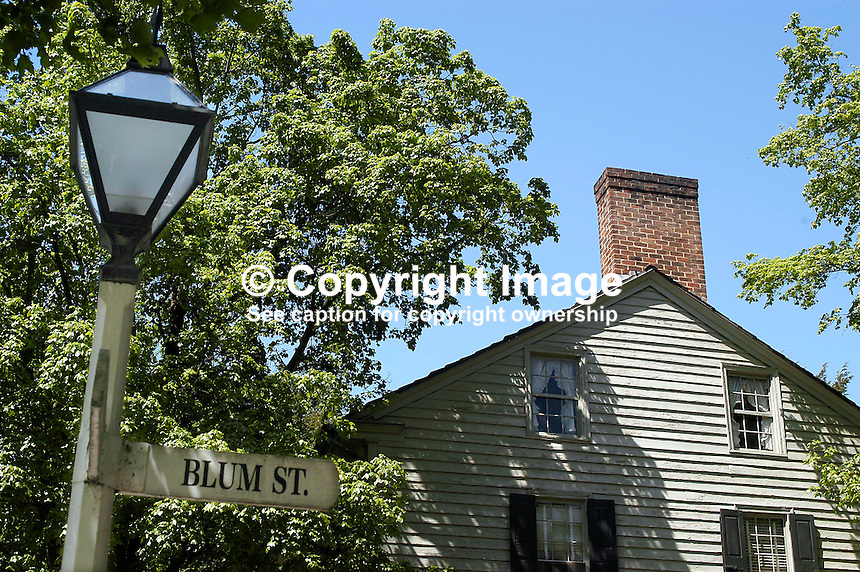 Old street lamp and street sign with timbered house and brick chimney in the background. Old Salem, North Carolina, USA - Although the Moravians had a presence in North Carolina from the 1750s the first buildings in Old Salem were commenced in 1766. The Moravians were religeous refugees from Bohemia in Europe. Bohemia is now part of the present Czech Republic. Since 1950 the town has been preserved to retain its character and old buildings were restored. Ref: 200304230067...Copyright Image from Victor Patterson, 54 Dorchester Park, Belfast, UK, BT9 6RJ..Tel: +44 28 9066 1296.Mob: +44 7802 353836.Voicemail +44 20 8816 7153.Skype: victorpattersonbelfast.Email: victorpatterson@mac.com.Email: victorpatterson@ireland.com (back-up)..IMPORTANT: If you wish to use this image or any other of my images please go to www.victorpatterson.com and click on the Terms & Conditions. Then contact me by email or phone with the reference number(s) of the image(s) concerned.
