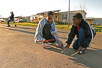 Canadaville, LA--Michael Lewis and Kaih Smith practice drumming on the pavement outside their new home in Canadaville. So far there is precious little to do in the new community. Liam Maloney / Special to The Gazette