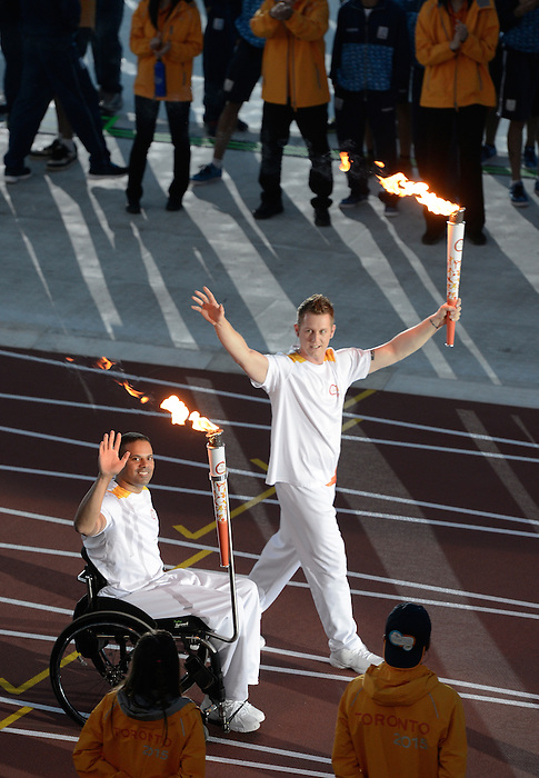 Toronto, ON - Aug 7 2015 - Sgt. Steve Daniel and Cpl. Dominic Larocque carry the flame into the stadium during the Opening Ceremonies for the Toronto 2015 Parapan American Games  (Photo: Matthew Murnaghan/Canadian Paralympic Committee)