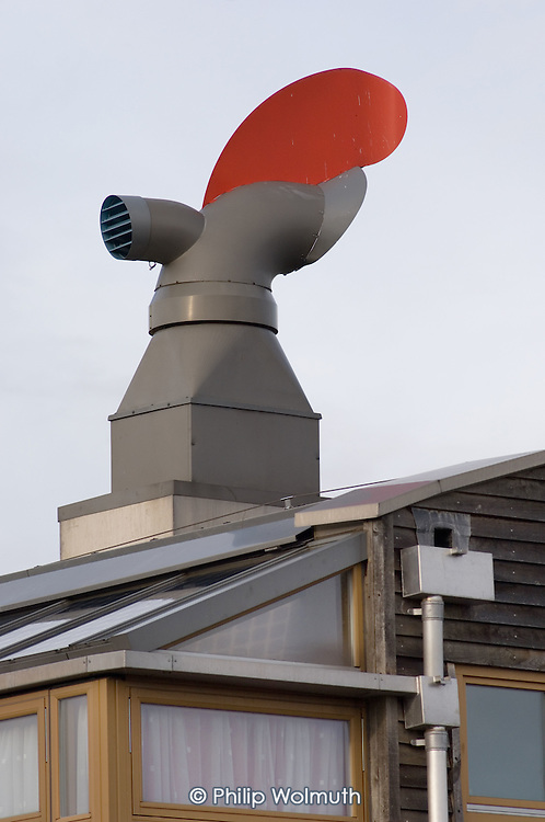 Rotating ventilation cowls and rain water collection pipes on the roof of a building at the Beddington Zero Energy Development (BedZED), in the London Borough of Sutton.  BedZED, the UK's largest carbon-neutral eco-community, comprises 82 mixed tenure housing units, managed by the Peabody Trust, and north-facing offices.