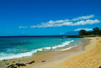 Clear blue water and a brilliant blue sky with wispy clouds frame the famous white sands of Makena Beach on Maui, this stretch known as  Little Beach.