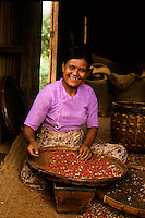 Portrait of a woman smiling while sorting coffee beans, Burma.