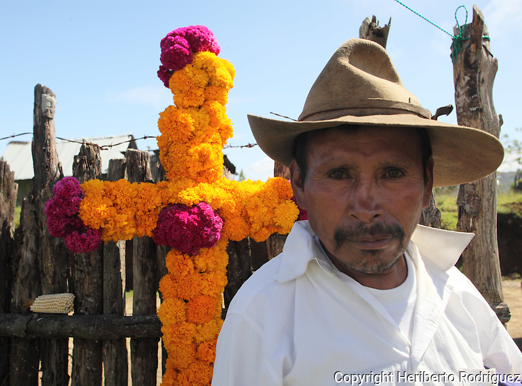 An old Native nahuatl peasant stands in front of a cross adorned with cempaxoxhitl flowers in Acaxochitlan village, in northern state of Hidalgo, during the festivities of the Day of the Deads. Hundreds of Native villages pay homage to their deads on the eve of November 2 as a tradition since the preHispanic times. Photo by Heriberto Rodriguez