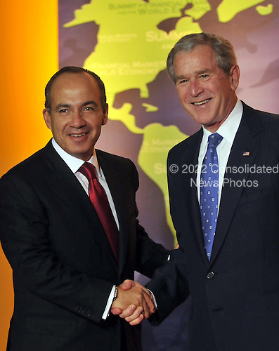 Washington, D.C. - November 15, 2008 -- United States President George W. Bush welcomes President Felipe Calderon Hinojosa of Mexico to the Summit on Financial Markets and the World Economy leaders to the National Building Museum in Washington, D.C. on Saturday, November 15, 2008..Credit: Ron Sachs / Pool via CNP