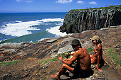 Torres, Rio Grande do Sul State, Brazil. man in shorts, girl in bikini sitting on the rocks by the sea.