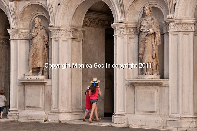 Two kids wearing hats like those of the gondoliers, walk through the courtyard of the Doge's Palace in Venice, Italy