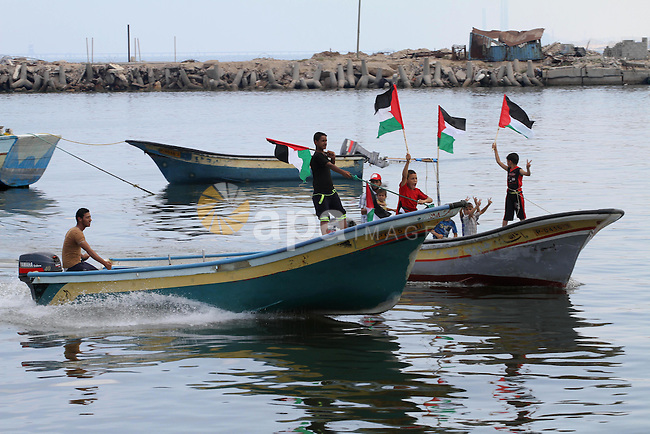 Palestinian children hold flags and banners during a rally to show solidarity with Third Freedom Flotilla in Gaza port on June 14, 2015. The flotilla is the third of its kind since 2010, when the first Freedom Flotilla was brutally attacked by Israel naval forces, who killed nine activists on board the ships. The incident, which took place in international waters, sparked international outcry. A second flotilla planned for 2011 was unable to reach Gaza after Greek authorities prevented the ships from leaving Athens. Photo by Mohammed Asad